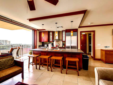 Kitchen with Bar, Stools, Armchair, Sofa, Refrigerator, and the Open Balcony.