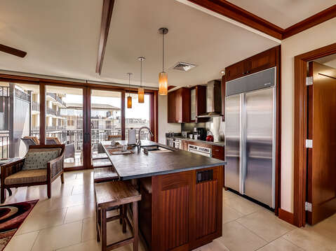 Kitchen Bar with Sink, Stools, Refrigerator, Armchair, Sliding Doors to the Balcony.