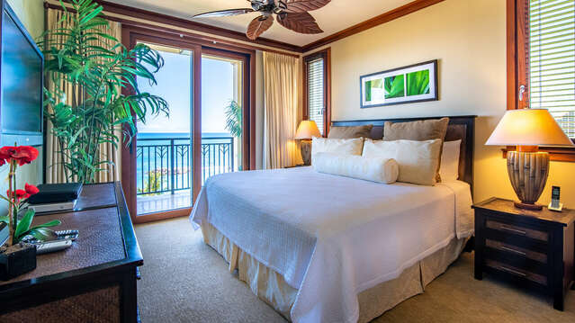 The Ko Olina Beach Villa's Master Bedroom with a King Size Bed, Lanai Access, Ceiling Fan & TV