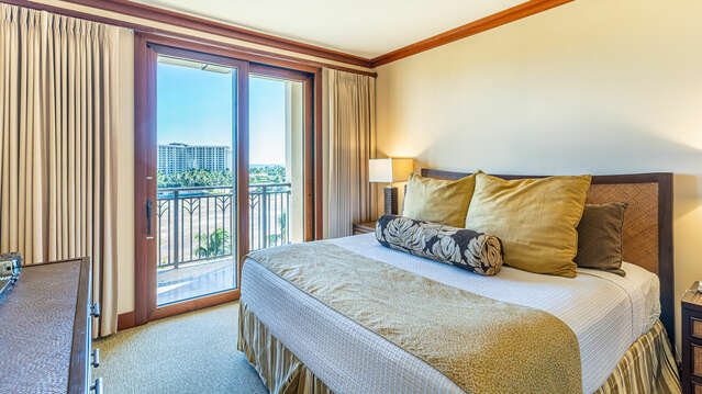 Master Bedroom of this Ko Olina beach villa for rent, with large bed, dual nightstands, and dresser with TV.