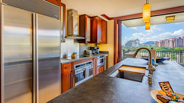 Fully Equipped Kitchen with ovens, wine fridge, full sized fridge, and center island with bar seating.