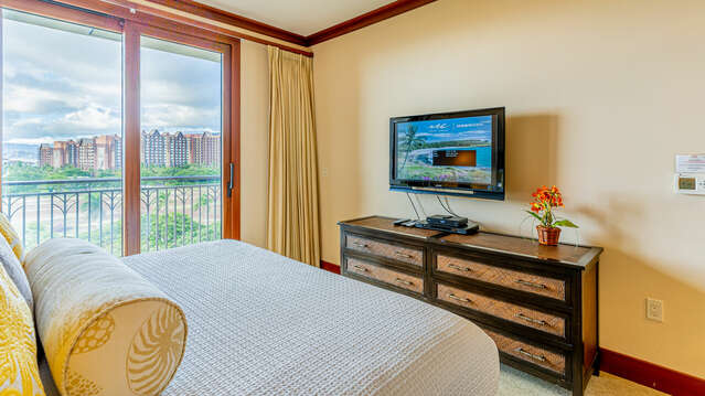 The Master Bedroom has Private Access to the Lanai, alongside large bed, dresser, and wall-mounted TV.