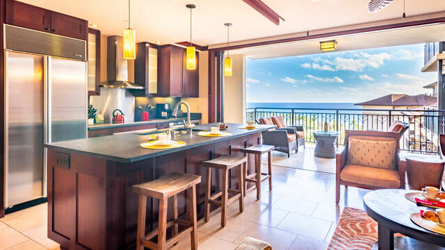 Kitchen with Island, Stools, the Balcony with Outdoor Chairs, Coffee Table, and Armchair.