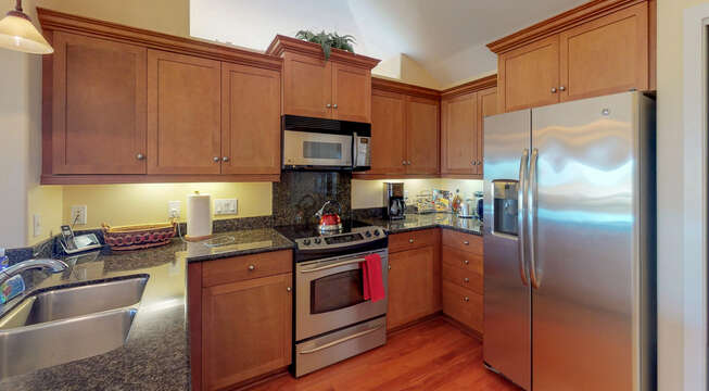 Angled photo of kitchen with sink, fridge, oven, and microwave in shot, displaying its granite counter-tops.