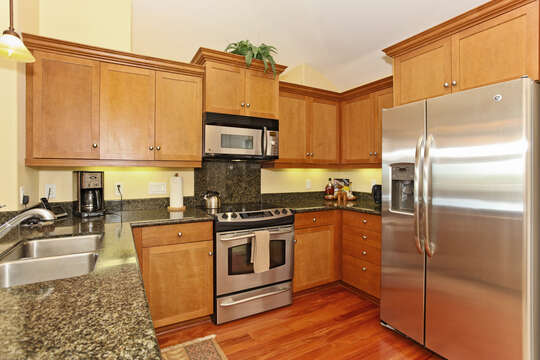 Kitchen with fridge, oven, and sink on granite countertops.