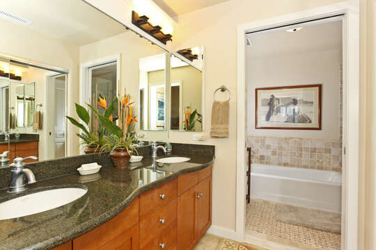 Bathroom with two sinks, large mirror, and door open to a separate room with a tub.