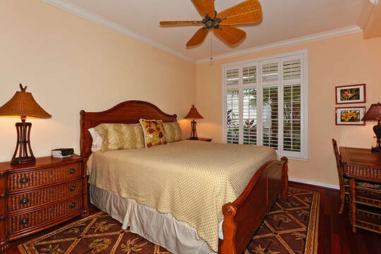 Large bed, side dressers with lamps, and table at the foot of the bed with chairs in one of the bedrooms of this Oahu condo rental.