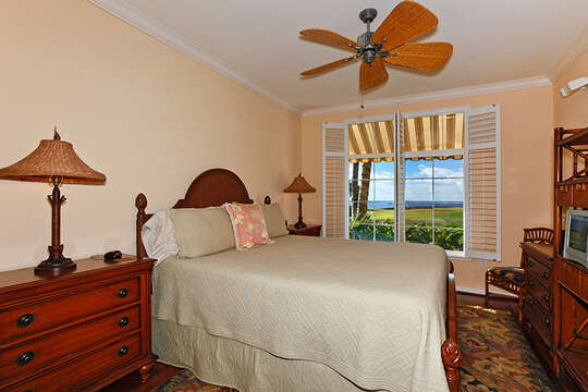 Bedroom with large bed, two side dressers with lamps, and entertainment center and TV>