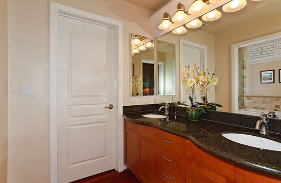 Bathroom with two sinks on the same counter, and large mirrors.