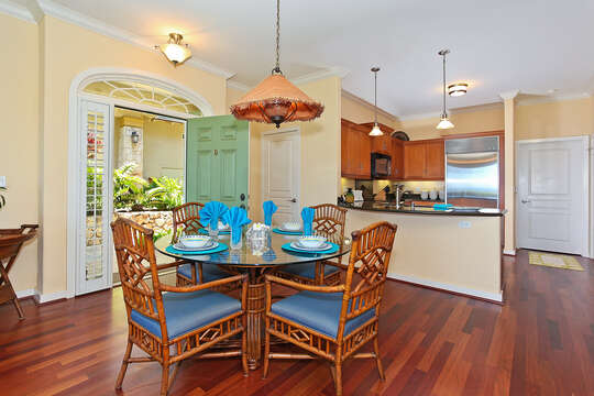 Glass-topped table, chairs, and open door leading into the dining area and kitchen of this Oahu condo rental.