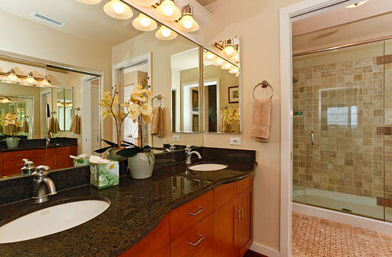 Bathroom in this Oahu condo rental with granite counter-top sinks, large mirror, and open door to a separate room with walk-in shower.