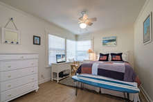 The second guest room at the rear corner of the house features a comfortable queen bed and television service.