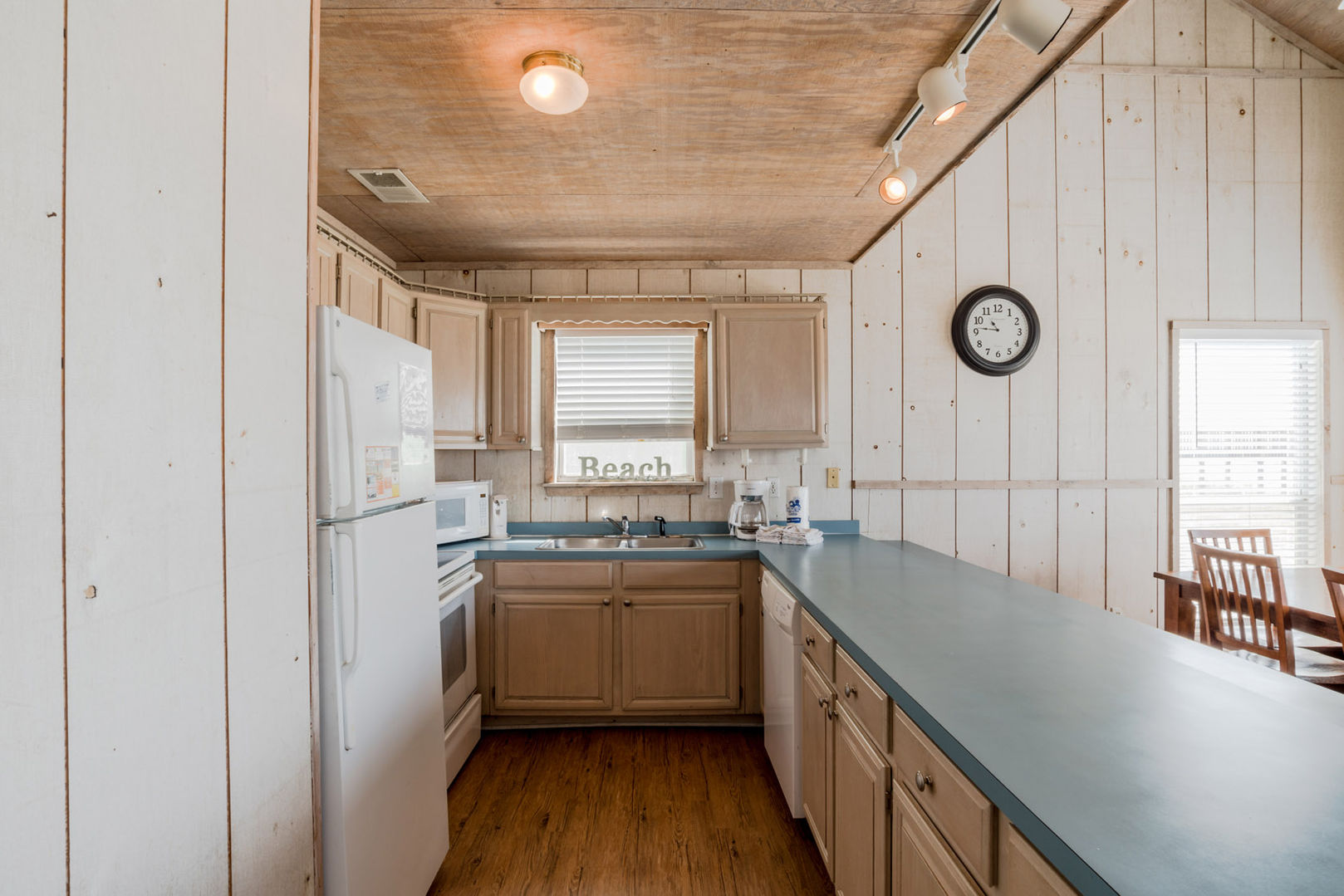 Kitchen with Counter, Refrigerator, Microwave, and Dining Set.