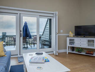 Sliding doors lead to a deck overlooking the water and beach.