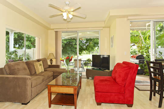 The Living Area of this Ko Olina condo rental with a View to the Golf Course, ample seating, and a TV.
