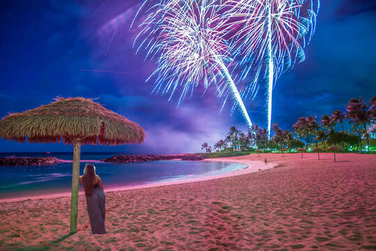 Fireworks over the lagoon, with a women enjoying the view from under an umbrella.