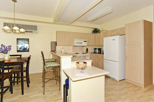 Large, Open Kitchen with fridge, extended counter-tops with bar seating, and oven.