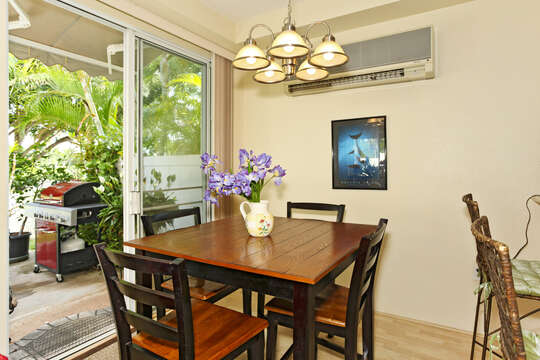 Dining Area with air conditioner above a dining table, chairs, and sliding glass door leading into the back yard.