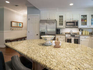 The open kitchen has granite counters, bar seating and a fridge with French doors.