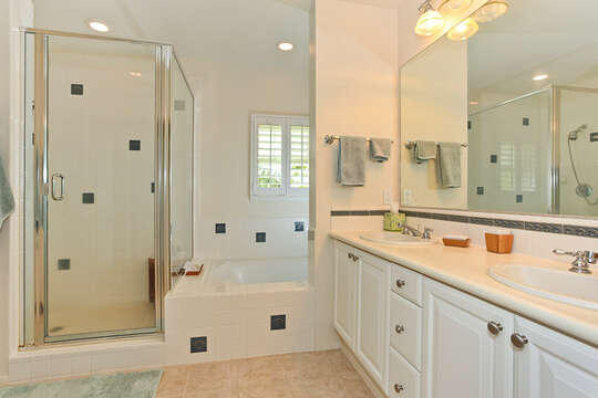 Bathroom with Walk- In Shower, Bathtub, and Double Vanity Sink.