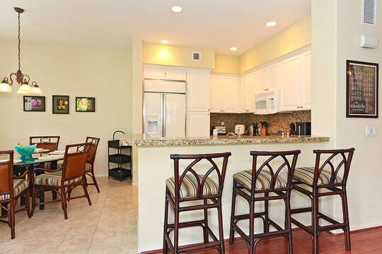 Kitchen Bar, High Chairs, Dining Table, Chairs, and Refrigerator.