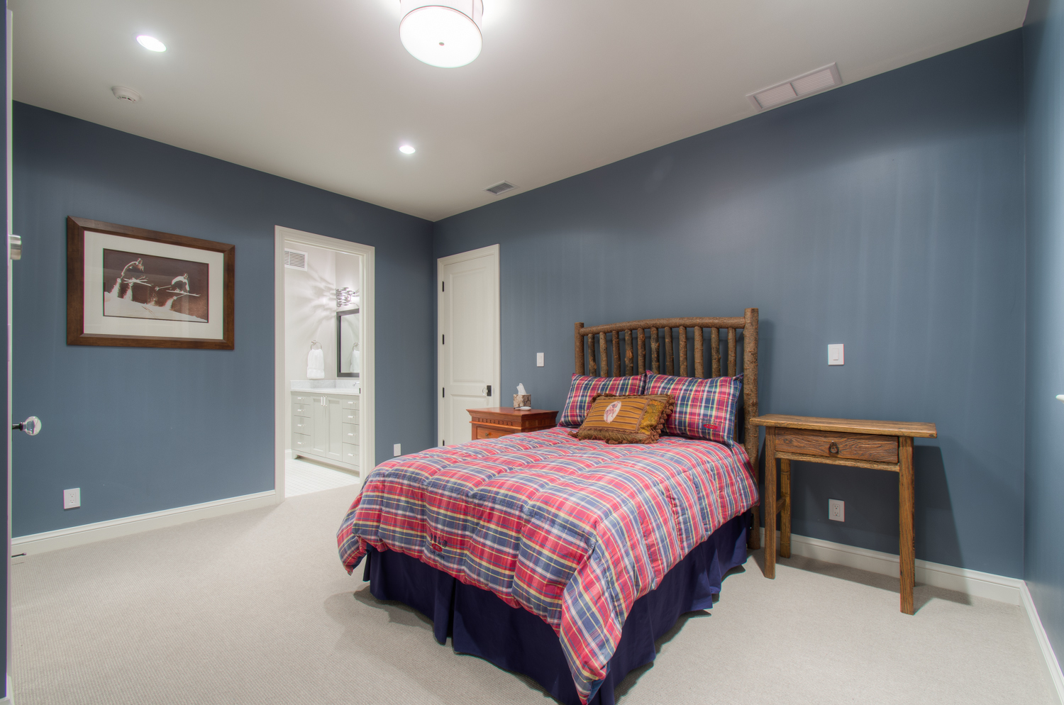 Spacious Bedroom with Plaid Linens and Blue Walls