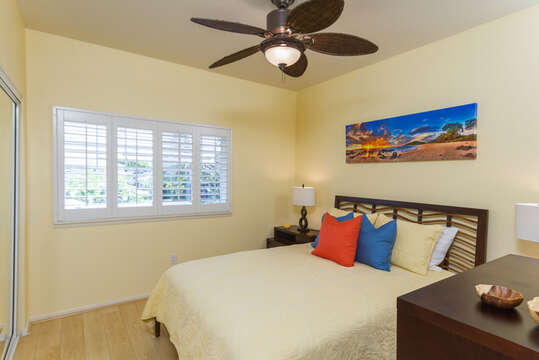 Bedroom with Large Bed, Dresser, Nightstands, and Ceiling Fan.