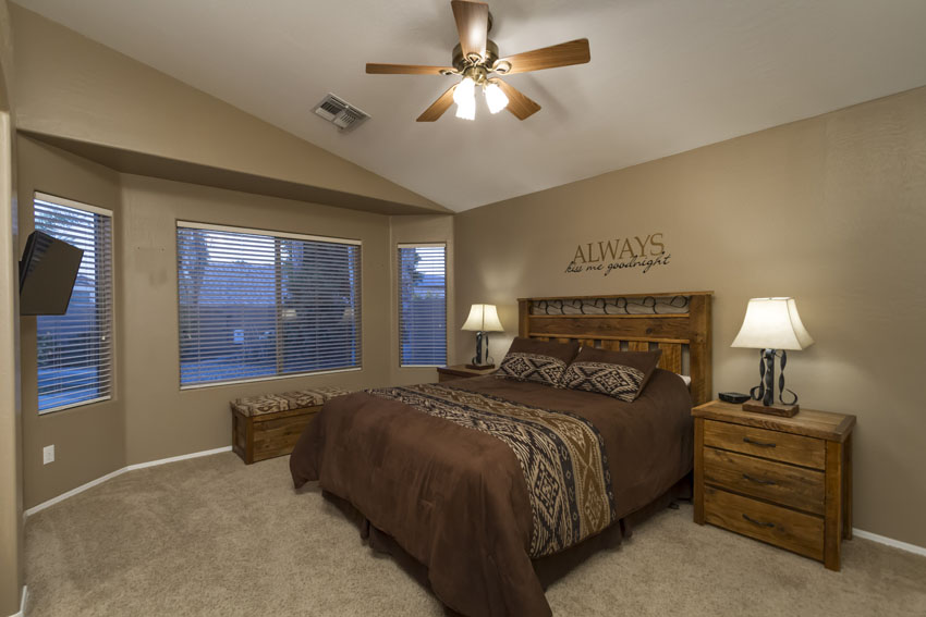 Master bedroom has a queen bed, bay windows overlooking pool, ceiling fan and two tables with lamps.