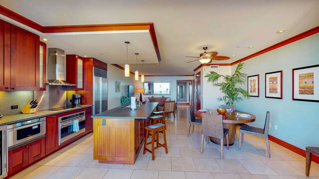 Kitchen with Bar, Oven, Refrigerator, Dining Table, Chairs, and Ceiling Fan.