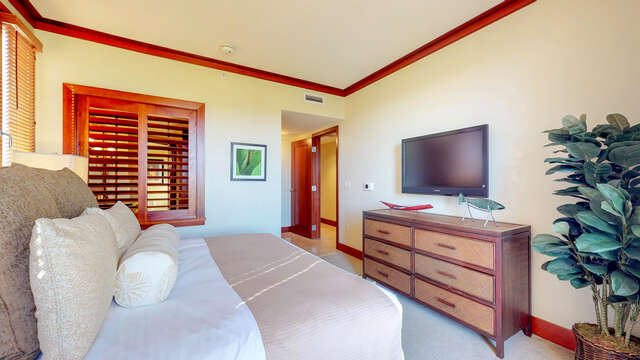 Bedroom with Large Bed, Drawer Dresser, and TV.