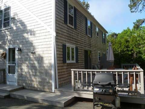 The back of the home offers a deck, dining area, and gas grill - 22 Happy Way Harwich Cape Cod New England Vacation Rentals