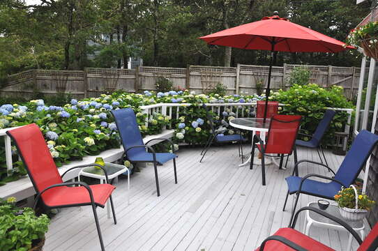 Outdoor deck with plenty of seating, table, umbrella and charcoal grill - 58 Longs Lane Chatham Cape Cod New England Vacation Rentals