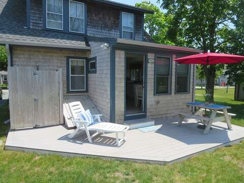 Outdoor picnic table with an umbrella and a chaise lounge. Also in the backyard, an enclosed outdoor shower - 36 Cross Street Harwich Port Cape Cod New England Vacation Rentals