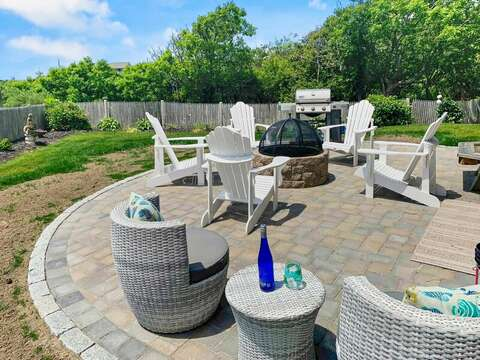 Grill, Fire pit and seating on the back yard patio at-19 Bob White Lane South Harwich Cape Cod New England Vacation Rentals