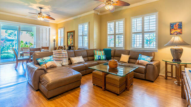 The living area, complete with sectional couch, glass topped coffee table, and dining area in the background.