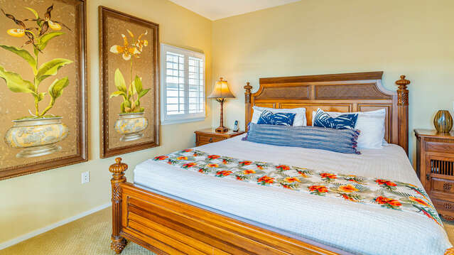 Bedroom with large bed, likewise large decorative wall hangings, and a nightstand. Door open to right to hallway.