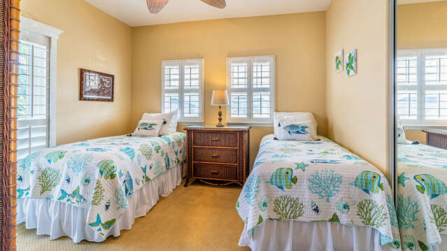 Two full beds side by side in one of this rentals bedrooms, with a nightstand in-between.