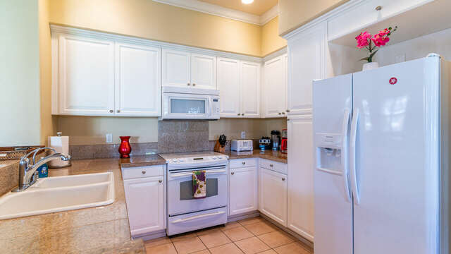 Kitchen of this condo for rent in Ko Olina Hawaii with fridge, oven, microwave, and sink built into the counter-tops.