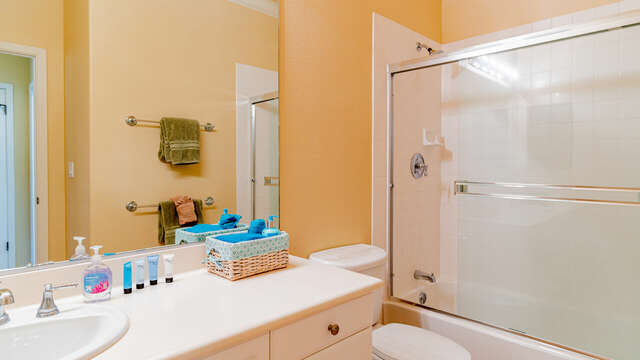 Bathroom in this condo for rent in Ko Olina Hawaii with a toilet, vanity sink, and shower with glass sliding door.