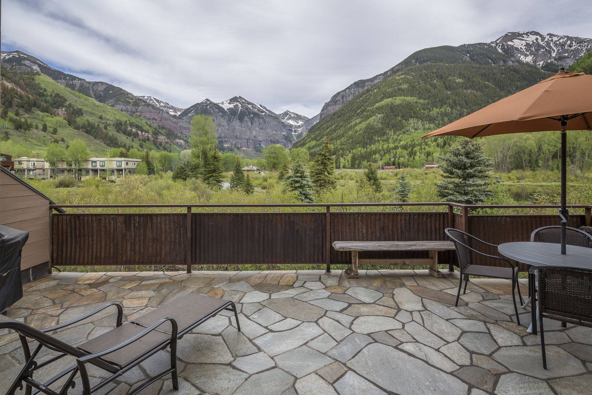 The balcony of this Colorado Mountain vacation rental, with ample seating and a covered table.