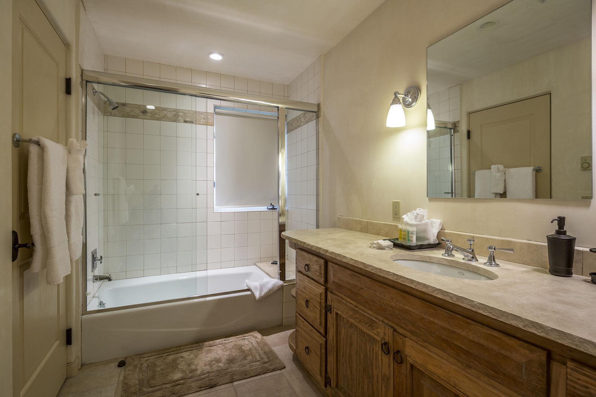 The glass-door shower of this bathroom is individual lit, as is the vanity sink.