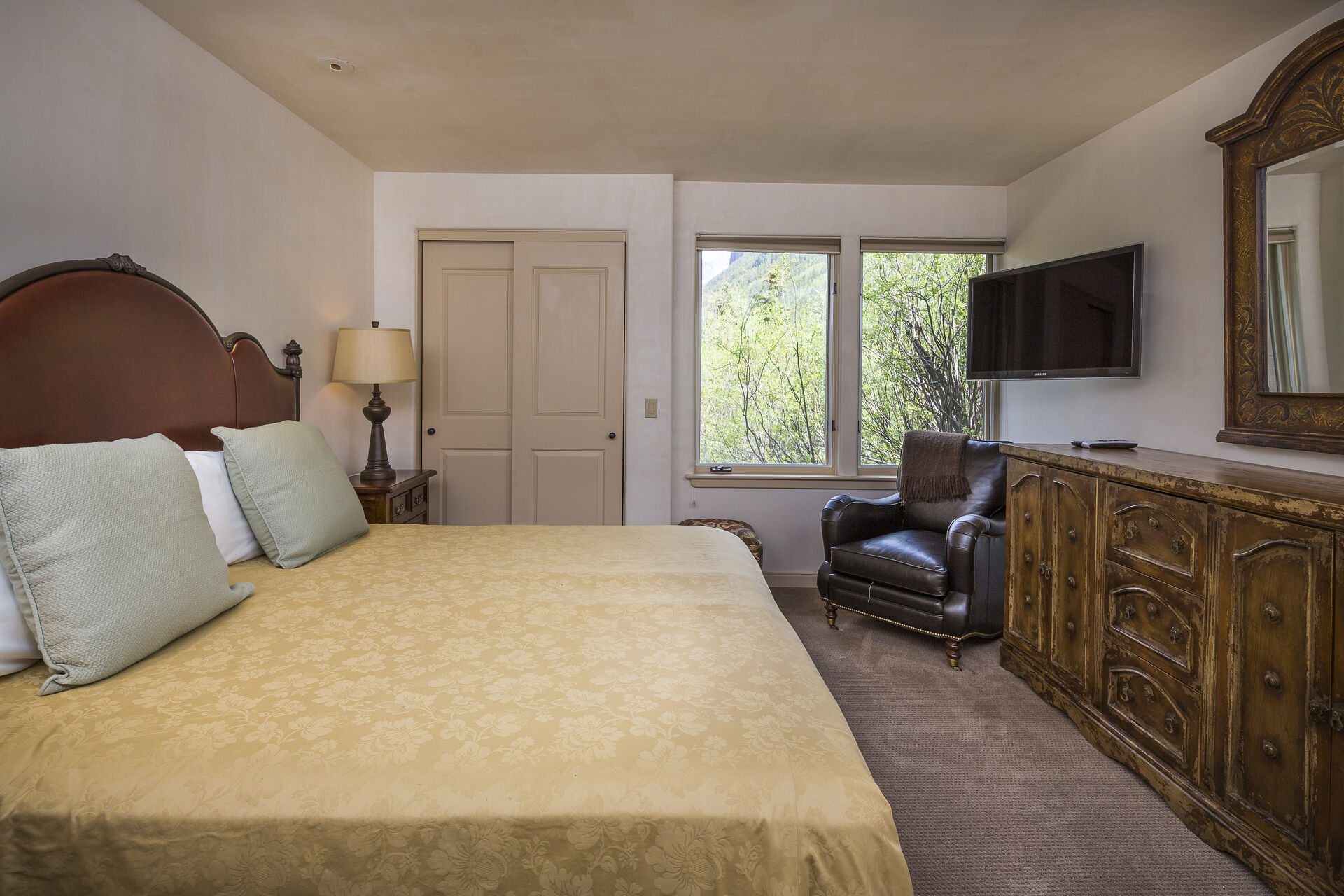 Vanity dresser, wall-mounted TV, and armchair by a large bed in a bedroom of this home.