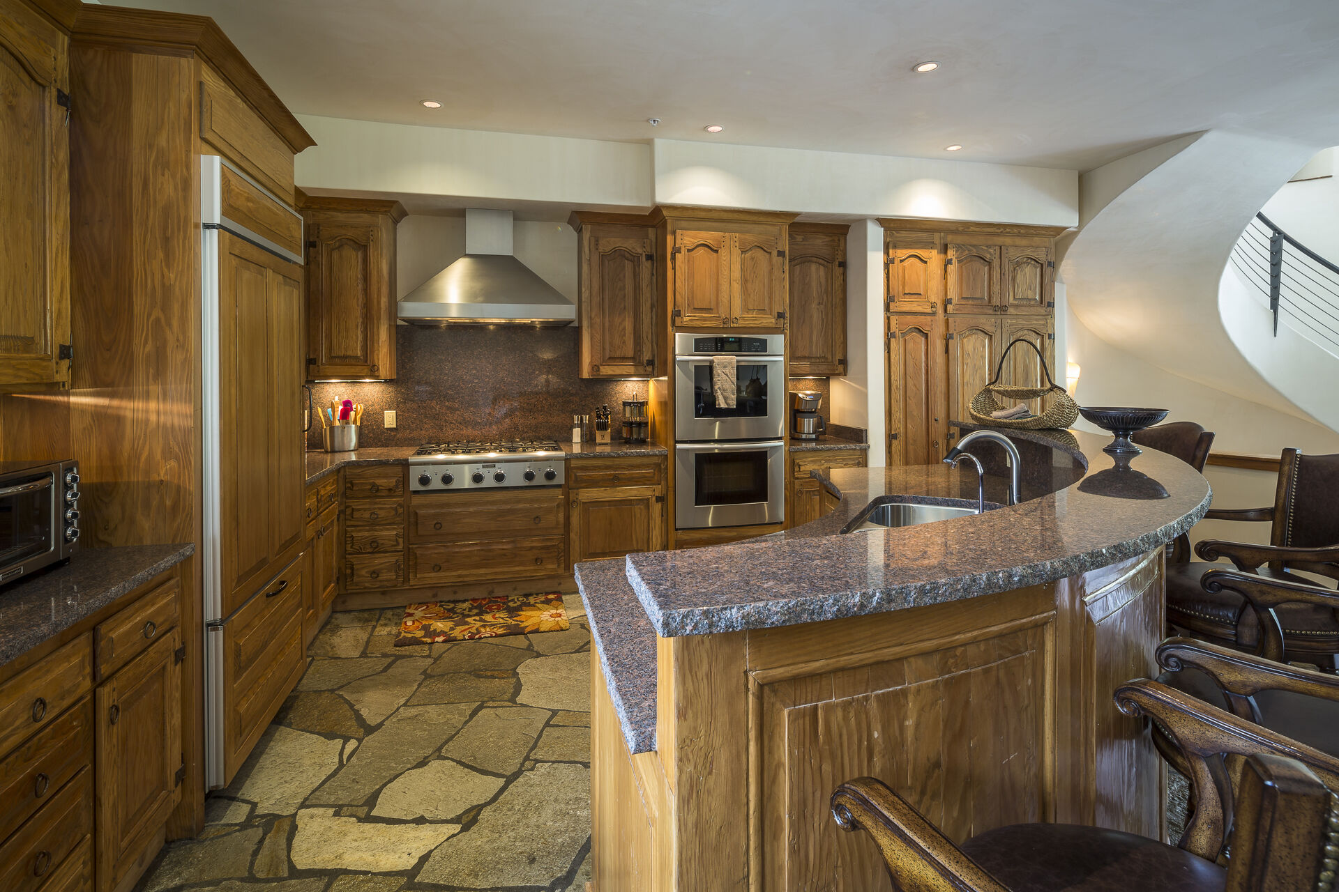 The fully equipped kitchen of this Colorado Mountain vacation rental, with bar seating and stainless steel appliances.