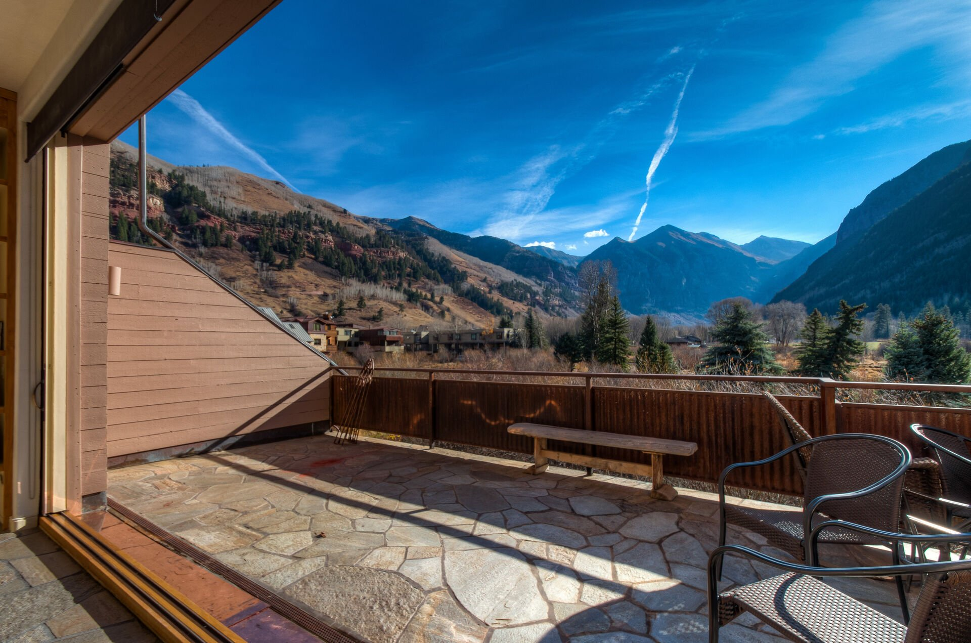 The balcony of this Colorado Mountain vacation rental, with chairs and a small bench.