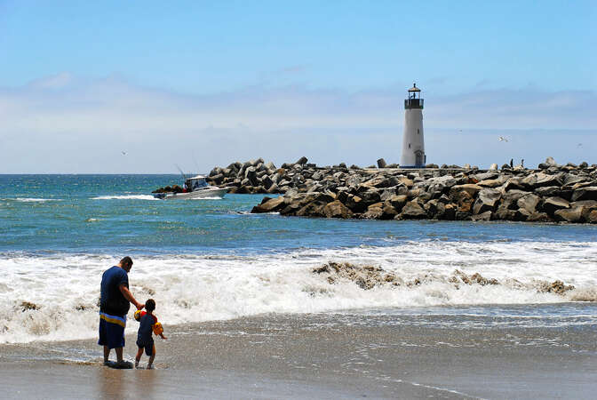Twin Lakes Beach and lighthouse at harbor entrance.