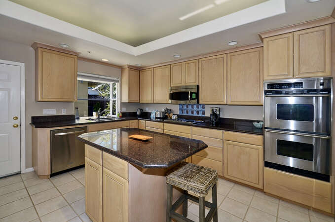 Kitchen with granite countertops, stainless steel appliances, and island.
