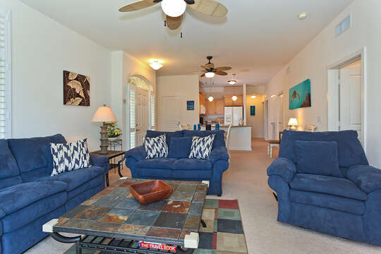 An Image of the Living Area with Two Blue Sofas and Chair.
