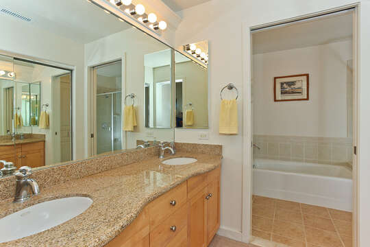 Master Vanity with Two Sinks and Open Door Leading to Separate Room with Bathtub.