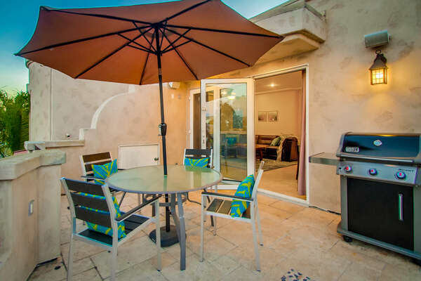 Upper-Level Patio with Grill and Outdoor Dining Set, and Table Umbrella.