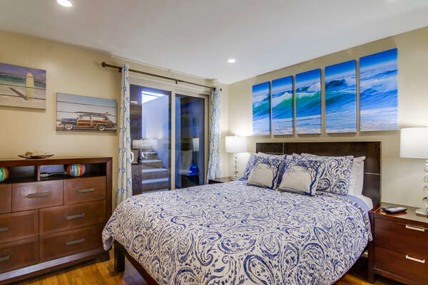 Master Bedroom with Queen Bed and ocean paintings above it.